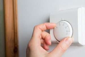 woman lowering the heating on her thermostat