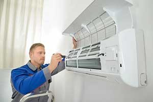 HVAC contractor preparing air conditioner for the summer