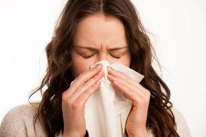 woman sneezing due to poor indoor air quality in her home