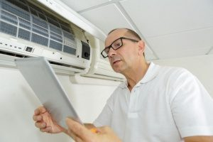 HVAC contractor in Gaithersburg, MD surveying an air conditioning unit while replacing air filters