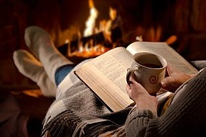 woman reading her book next to the fireplace with hot chocolate in the winter time due to very low humidity in the air as well as relatively cold temperatures