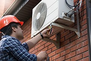 a Gaithersburg, MD HVAC contractor working on an outdoor HVAC unit to increase the indoor air quality in the home