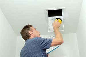 HVAC contractor inspecting ductwork in a house that utilizes forced air furnaces
