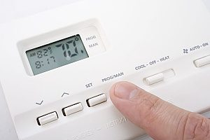 a man turning down his thermostat to allow his heating system to work during the winter