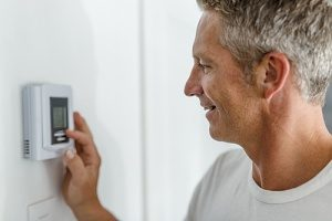 Man adjusting his heater to the exact temperature he wants after getting a new heat pump installed by a heating installation specialist
