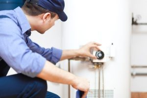 plumber fixing hot water heater as part of routine heating repair