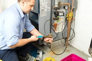 technician performing a furnace installation of a gas furnace