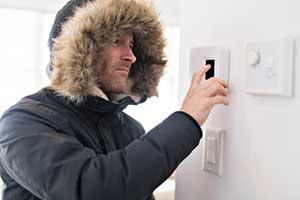 man checking thermostat because his heat wont turn on