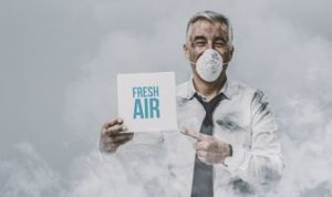 man wearing a surgical mask and holding a sign that reads fresh air