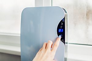 a woman using a dehumidifier to combat high humidity levels in her home