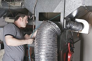 a man cleaning mold out of his ductwork with the help of an HVAC contractor