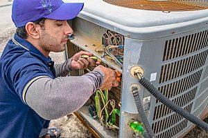 a professional HVAC contractor servicing an AC unit