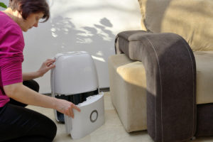 a woman emptying the extracted water out of a portable dehumidifier