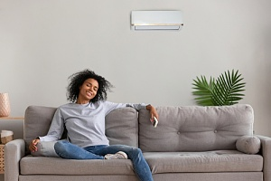 woman on couch enjoying central air conditioning