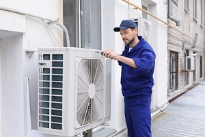 worker installing air conditioning for the summer