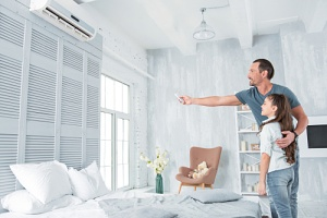 father helping his daughter set the air conditioner