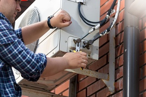 technician fixing a new air conditioner cost