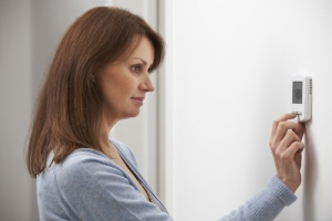 Woman lowering thermostat to save energy before going to work
