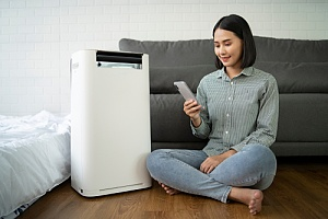 Woman turning on her dehumidifier