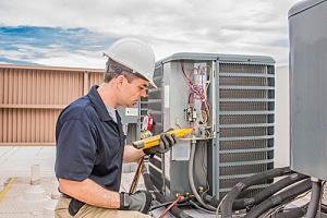 HVAC technician working on unit