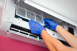 a person cleaning an AC unit which is good to do if your AC unit stops working