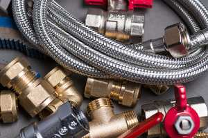 Assorted plumbing fittings and hose for dehumidifier on grey surface that has been repaired