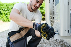 HVAC professional performing an air conditioning installation at a residential home