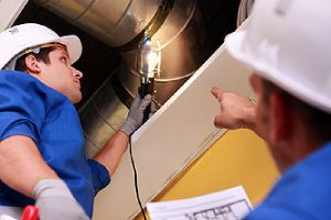 Two HVAC technicians conducting air duct inspection