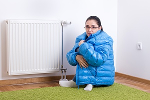 a woman who needs a heating repair huddled next to a radiator heater on the floor